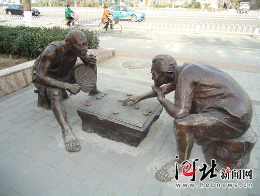 """雕塑下棋的""""老人""""吸引路人目光(图)"""